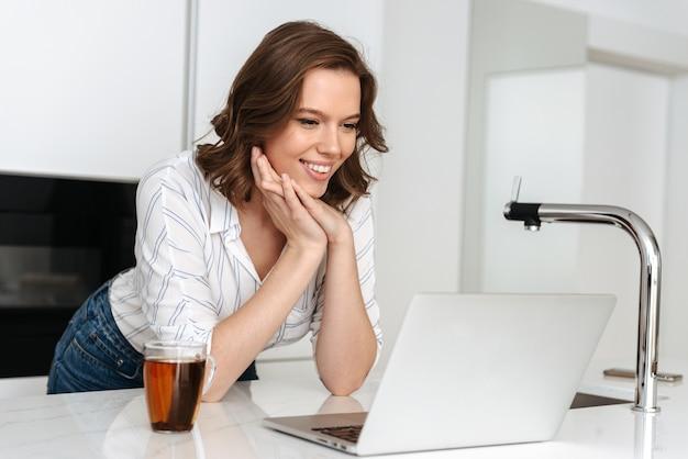 自宅のキッチンに立って、ラップトップコンピューターで作業し、お茶を飲む幸せな若い女性