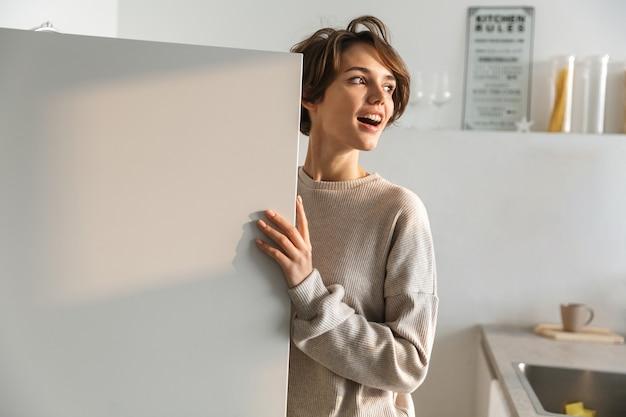 열린 된 냉장고에 서 행복 한 젊은 여자