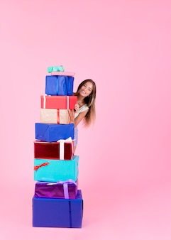 Happy young woman standing behind the stack of different gift boxes on pink backdrop
