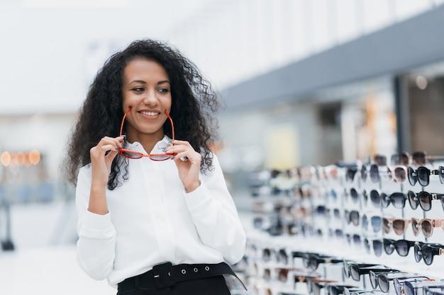 Счастливая молодая женщина, стоящая в магазине оптометрии