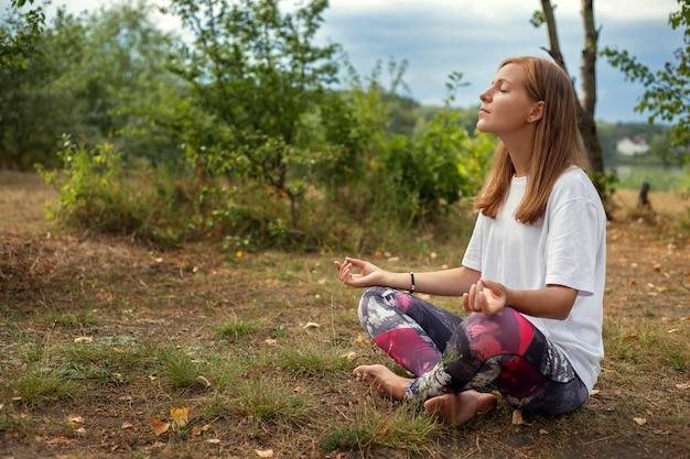 公園の芝生の上のヨガのポーズで立っている幸せな若い女