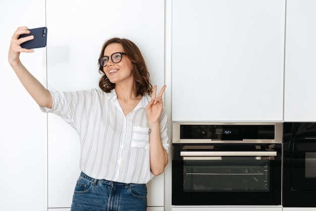 Happy young woman standing at the kitchen at home, taking a selfie