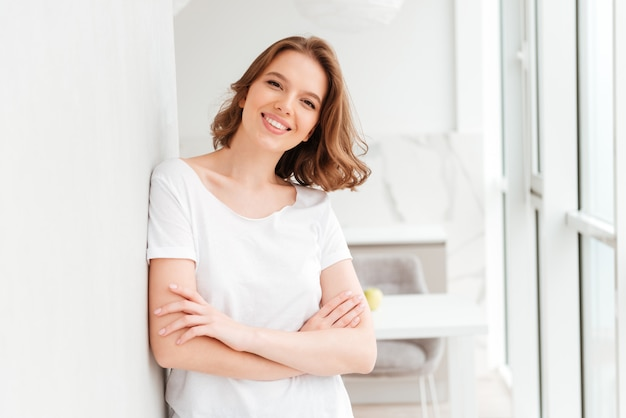 Happy young woman standing near window with arms crossed