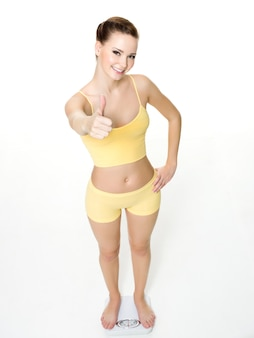 Happy young woman standing on scales and shows the thumbs-up isolated on white. high angle view