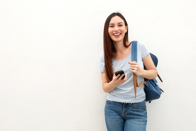 Happy young woman standing with backpack and mobile phone