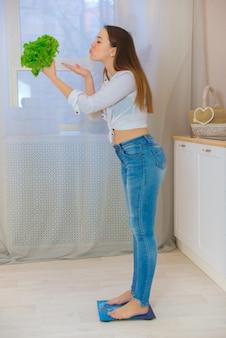 화장실에 행복 한 젊은 여자 단계는 과체중 문제를 조정