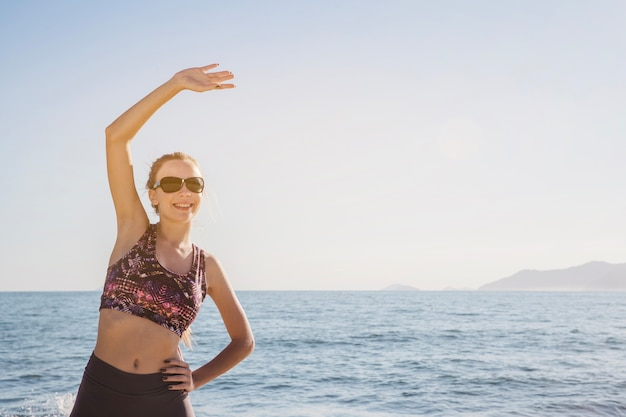 Happy young woman stretching on the beach