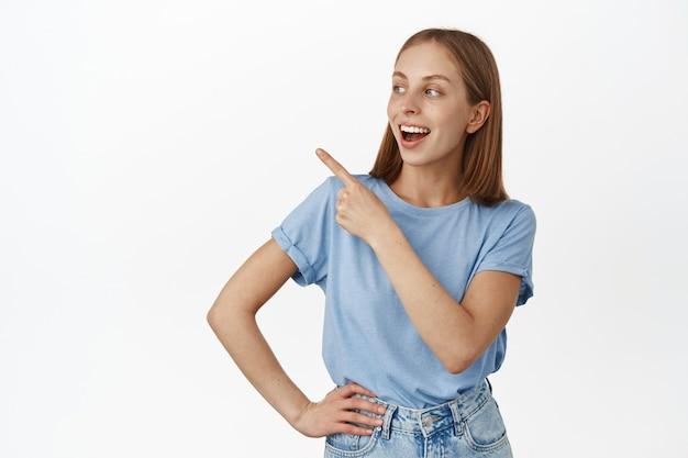 행복한 젊은 여성, 걱정 없는 얼굴로 왼쪽 상단을 가리키고 바라보는 학생, 재미있는 광고, 판매 배너, 흰 벽 위에 서 있는