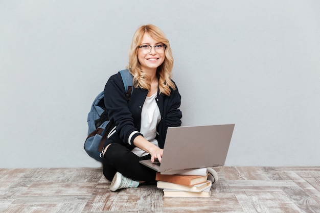 Studente felice della giovane donna che per mezzo del computer portatile.