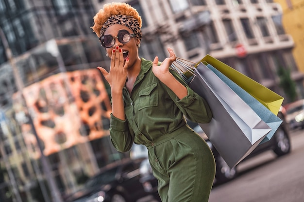 Happy young woman in sunglasses with shopping bags walking in the city with buildings on the background