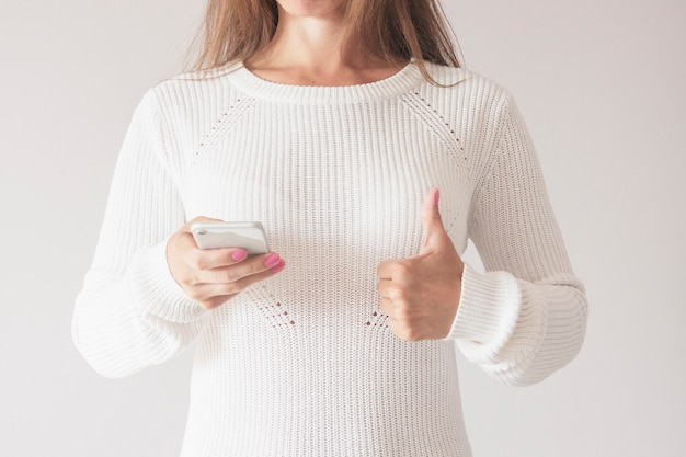 Happy young woman in sweater with smart phone thumb up
