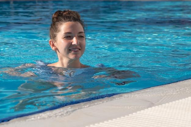 幸せな若い女性は太陽の下でプールで泳ぐ。