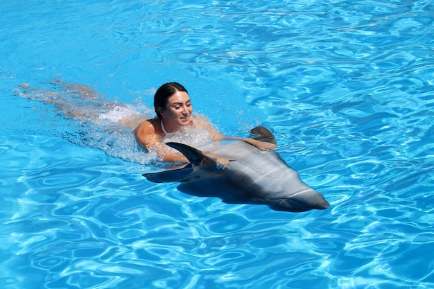 Happy young woman swims with dolphin in blue water.