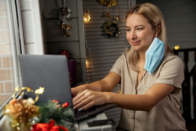 행복 한 젊은 여자는 보호 마스크를 벗고 확대 / 축소를 사용 하여 메리 크리스마스 그녀의 친척을 축 하합니다. 집에서 노트북으로 얼굴 시간 화상 통화를 할 수 있습니다.