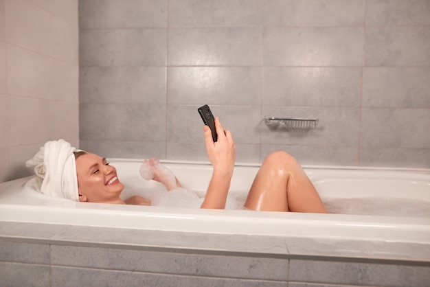Happy young woman taking bath with foam and speak by video call