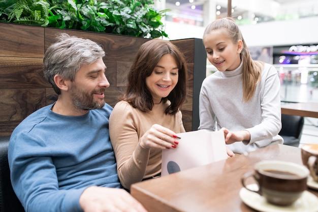 彼女の娘と夫がカフェで休憩中にそばに座っている間、paperbagでギフトを見て幸せな若い女