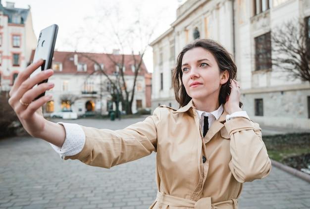 街の通りでselfieを取る幸せな若い女性。屋外を歩く幸せな観光客の女の子。旧市街でポーズをとるかわいいブルネットの女性の春のファッションの肖像画。