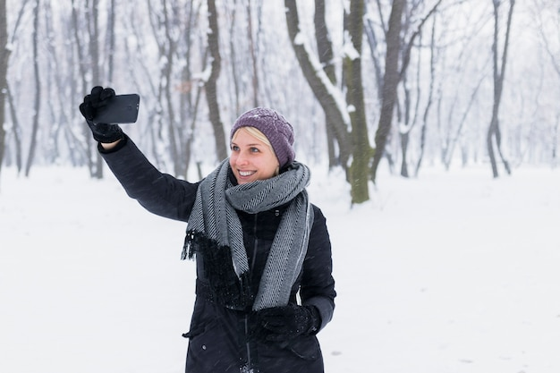 Happy young woman taking selfie in forest during winter
