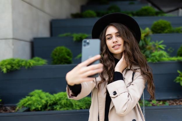 도시 거리에 평화 기호 selfie를 복용하는 행복 한 젊은 여자