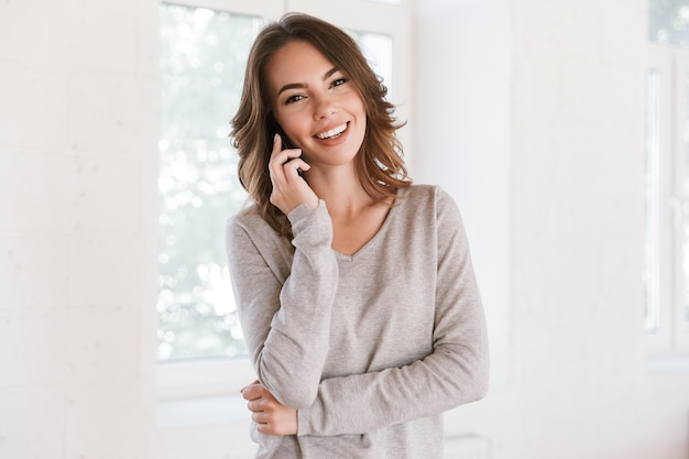Счастливая молодая женщина разговаривает по мобильному телефону