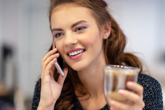 自宅でスマートフォンで話している幸せな若い女性。屋内で電話をかける魅力的な女性。