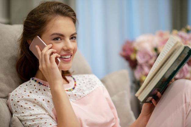 Счастливая молодая женщина разговаривает по умному телефону дома. привлекательная женщина, звоня по телефону в помещении.