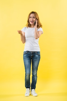 Happy young woman talking on mobile phone against yellow backdrop