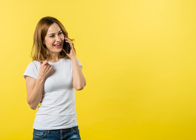 Happy young woman talking on mobile phone against yellow background