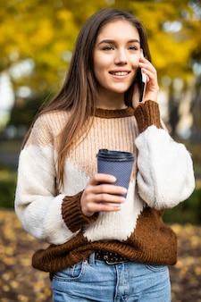 電話で話している、持ち帰り用のコーヒーカップを押しながら笑って幸せな若い女。