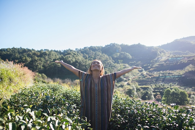Happy young woman on tea plantation