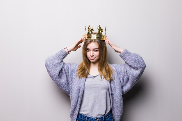 Happy young woman or teen girl in princess crown isolated on gray