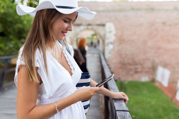 Happy young woman texting sms outdoors.