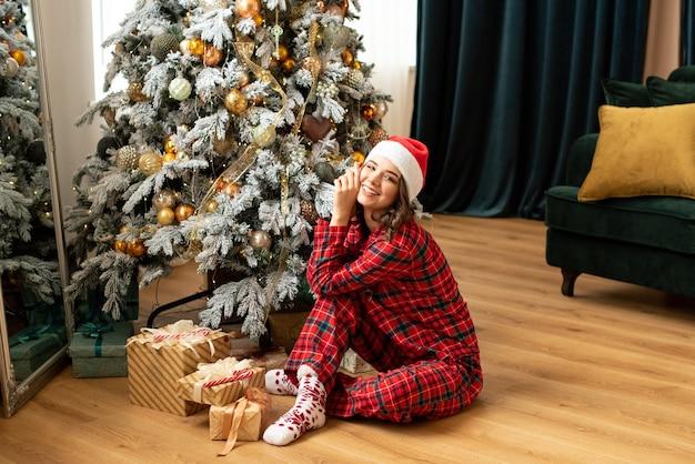 크리스마스 트리 근처에 선물을 던지고 행복 한 젊은 여자. 그녀는 선물과 선물 근처에 앉아 있습니다. 트렌드 컬러는 포르투나 골드와 타이드워터 그린.