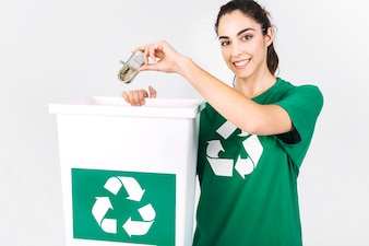 Happy young woman throwing mini tiffin box in recycle dustbin