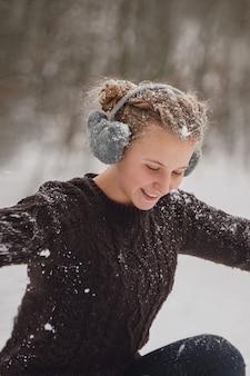 솜털 헤드폰과 서리가 내린 겨울 공원에서 재미 니트 스웨터에 눈 아름다움 겨울 아가씨를 던지고 행복 한 젊은 여자 야외 비행 눈송이 좋은 분위기 겨울 크리스마스 휴일 개념