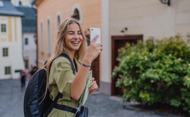 スマートフォンで自分撮りをしながら、町の旅行で屋外で幸せな若い女性の観光客。