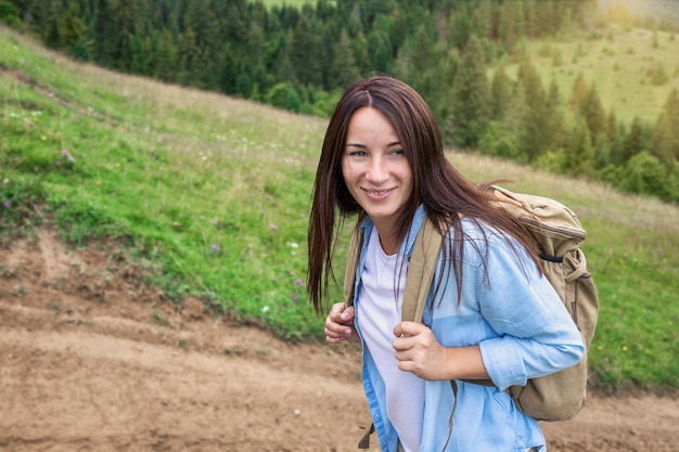 Happy young woman tourist walks with backpack in the highlands. active lifestyle concept