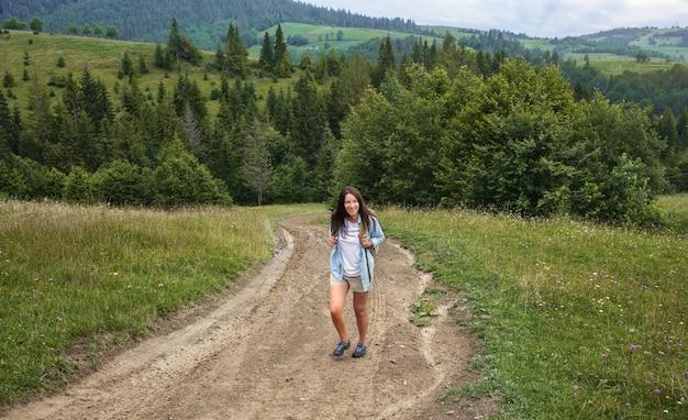 幸せな若い女性の観光客は、高地でバックパックを持って歩きます。アクティブで健康的なライフスタイルのコンセプト