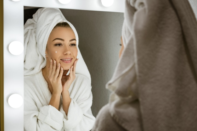 A happy young woman in a towel in front of a mirror applies cream to her face, a concept of skin care at home