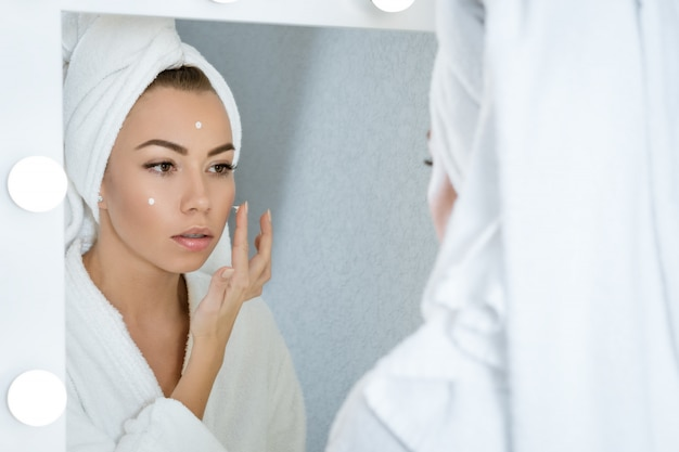Happy young woman in a towel in front of  mirror applies cream to her face, a concept of skin care at home