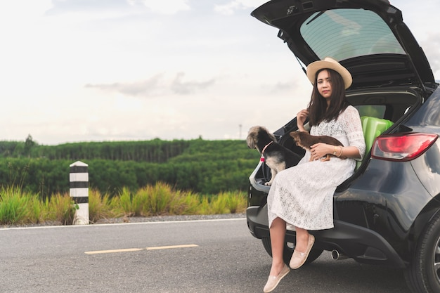 Happy young woman traveler sitting in car with dogs on road and sunset sky.
