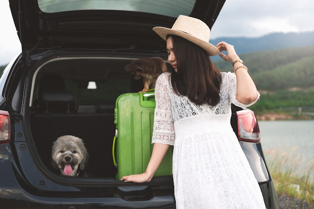 Happy young woman traveler sitting in hatchback car with dogs.
