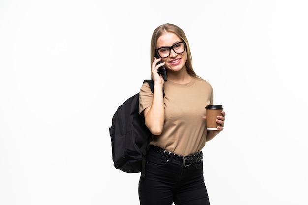 Студент университета счастливая молодая женщина с рюкзаком и книгами разговаривает по мобильному телефону, изолированному на белой поверхности