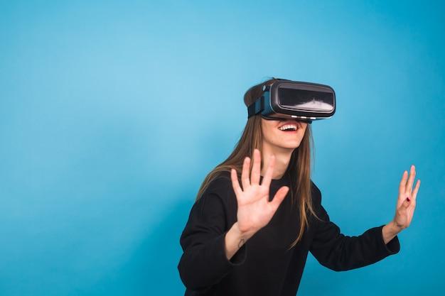 青の仮想現実ヘッドセットを使用して幸せな若い女
