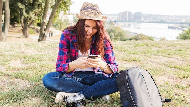 Happy young woman using cellphone in park
