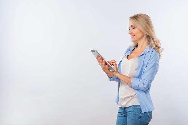 Счастливая молодая женщина с помощью цифрового планшета на белом фоне