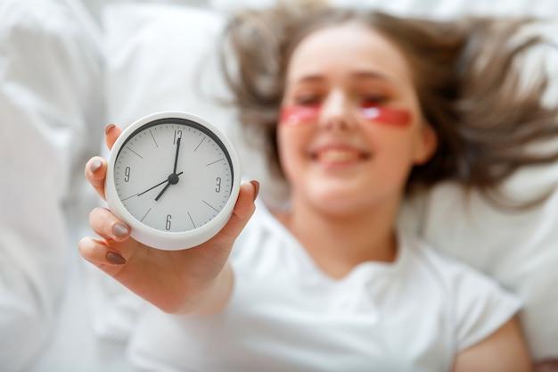 ベッドサイドの目覚まし時計を手に持って眠った後、幸せな若い女性が目を覚ます。パジャマ姿の朝の美容ルーチン。目覚まし時計から目が覚めた後、女性は眼帯を使用します。健康的な睡眠。