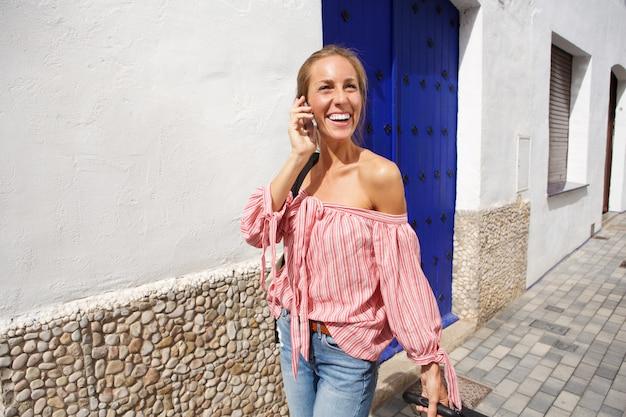 携帯電話で歩くと話している幸せな若い女性