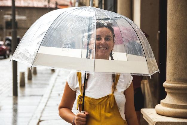 비오는 날 우산을 들고 도시를 산책하는 행복한 젊은 여성.