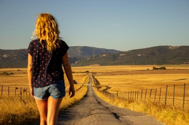 시골에서 걷는 행복 한 젊은 여자